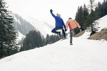 Austria, Damuels, happy senior couple jumping in winter landscape - PNPF00044