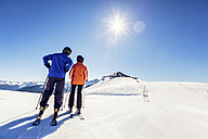 Austria, Damuels, couple with skiers in winter landscape - PNPF00053