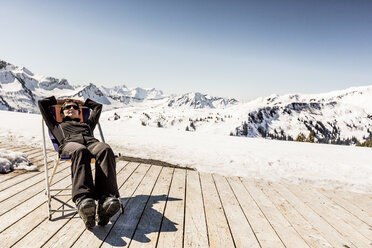 Austria, Damuels, woman relaxing in deckchair on sun deck in winter landscape - PNPF00056