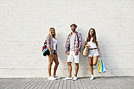 Portrait of three friends standing at white wall with bags - JRFF01445