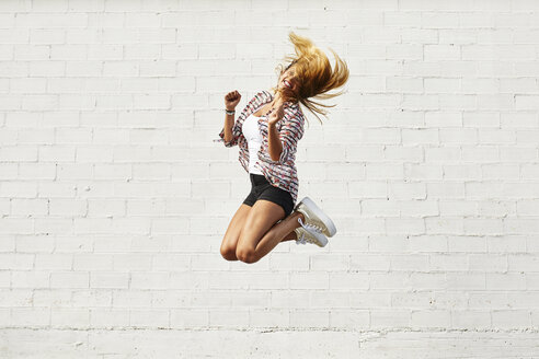 Happy young woman jumping mid-air in front of white wall - JRFF01448
