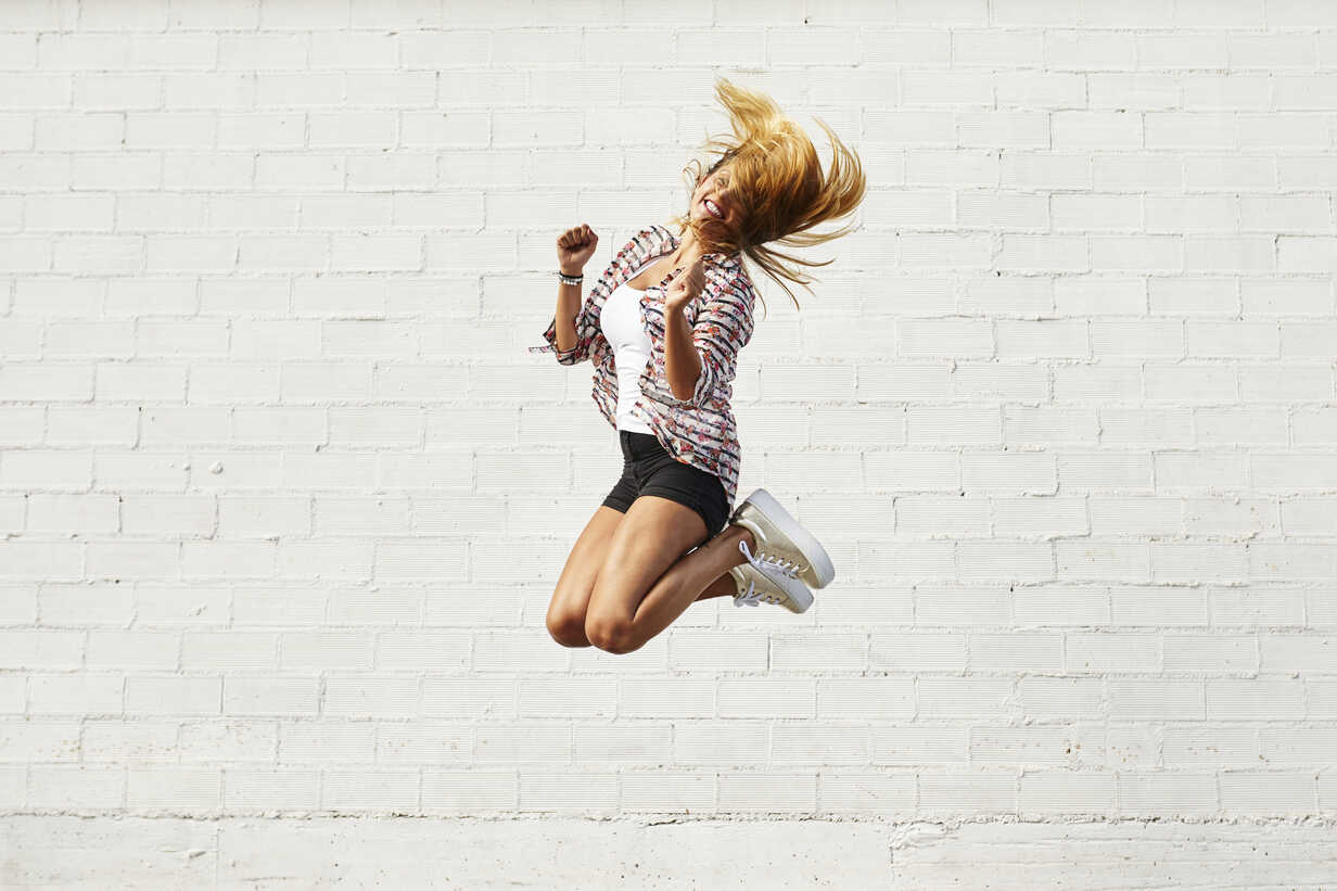 Happy young woman jumping mid-air in front of white wall - JRFF01448 - Josep Rovirosa/Westend61