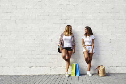 Two young women standing at white wall with bags - JRFF01451