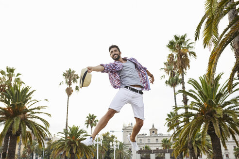 Spain, Barcelona, happy man jumping mid-air surrounded by palm trees - JRFF01463
