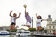 Spain, Barcelona, three friends jumping in the city center near the sea - JRFF01472