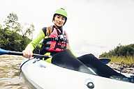 Germany, Bavaria, Allgaeu, portait of confident young woman kayaking on river Iller - PNPF00062