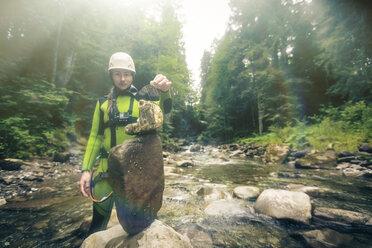 Germany, Bavaria, Allgaeu, young woman building heap of stones in Ostertal - PNPF00083