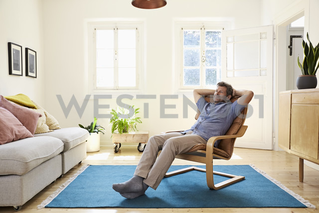 Man relaxing at home sitting in arm chair - PDF01283