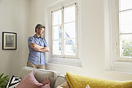 Mature man at home eaning at window - PDF01295