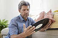 Mature man at home sitting in front of couch, looking at old vinyl record - PDF01313