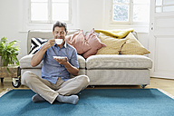 Man sitting on floor, drinking coffee - PDF01316