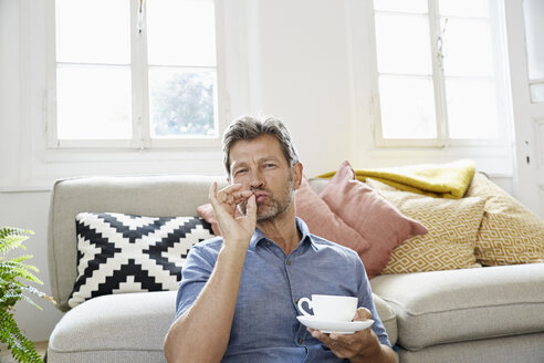 Mature man at home sitting in front of couch, drinking coffee - PDF01319