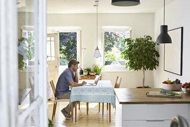 Mature man sitting in his dining room, using laptop - PDF01334