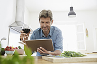Mature man in his kitchen reading recipe on his digital tablet - PDF01346