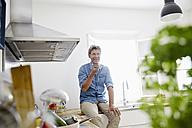 Mature man in his kitchen sing smartphone - PDF01352