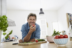 Mature man in his kitchen eating tomato - PDF01355
