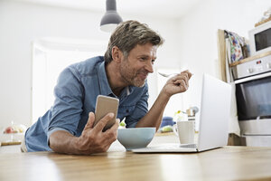 Mature man in his kitchen having breakfast, while checking his laptop - PDF01361