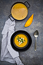 Soup dish of creamed pumpkin soup with croutons and parsley and pumpkin soup in cooking pot - LVF06284