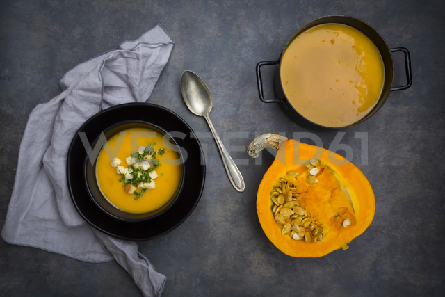 Soup dish of creamed pumpkin soup with croutons and parsley, half of pumpkin and pumpkin soup in pot - LVF06287