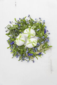 White eggs with green bows in nest of Forget-me-not, Muscari and pussy willows on white background - GWF05248