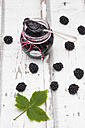 Glass of homemade blackberry jam, blackberries and leaf on wood - LVF06290