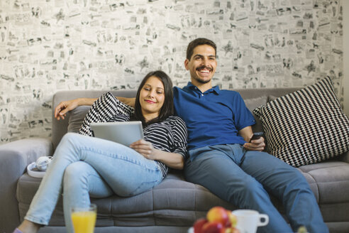 Couple sitting on the couch using tablet and watching television - MOMF00250
