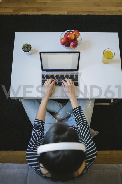 Young woman using laptop and headphones at home, top view - MOMF00253