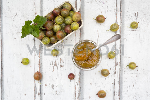 Cardboard box of gooseberries and jar of gooseberry jam on wood - LVF06296