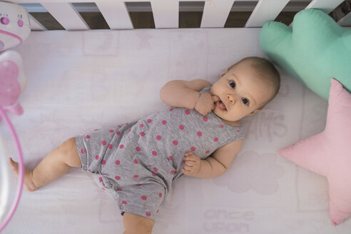 Cute baby girl lying in crib - MOMF00260