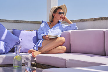 Woman with book relaxing on sun deck - DIKF00287