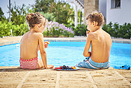 Two children eating fruit at the poolside - DIKF00290