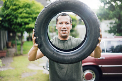 Portrait of smiling man holding car tyre - MOEF00163