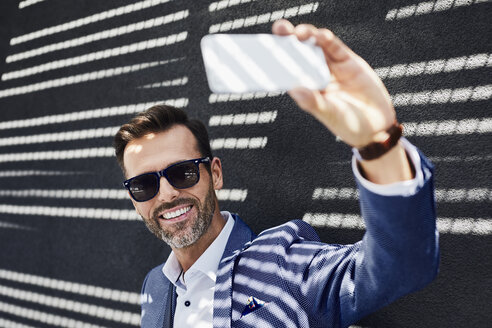 Businessman taking selfie with smartphone outdoors - BSZF00005