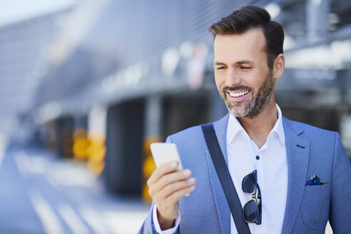 Businessman using phone on parking level outdoors - BSZF00011