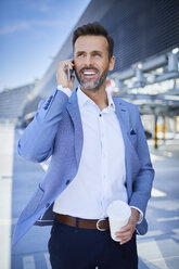 Businessman with coffee talking on phone in the city - BSZF00020