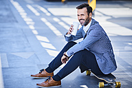 Businessman drinking coffee and sitting on longboard - BSZF00023