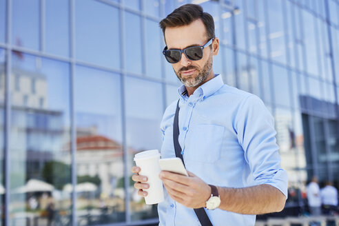 Businessman using phone and holding coffee outdoors - BSZF00029