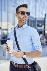 Businessman looking away outdoors holding phone and coffee - BSZF00032