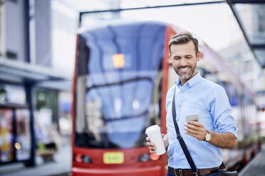 Businessman using phone after getting off public transport - BSZF00035