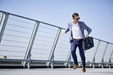 Businessman with coffee and briefcase running - BSZF00044