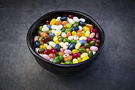 Bowl of colourful sweet jellybeans on grey background - LVF06304