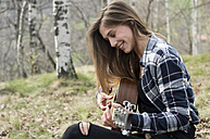 Smiling woman playing guitar in forest - ZOCF00512