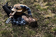 Woman lying on meadow playing guitar - ZOCF00515