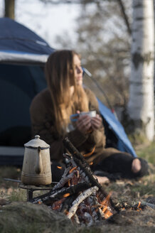 Woman camping at campfire in forest - ZOCF00518