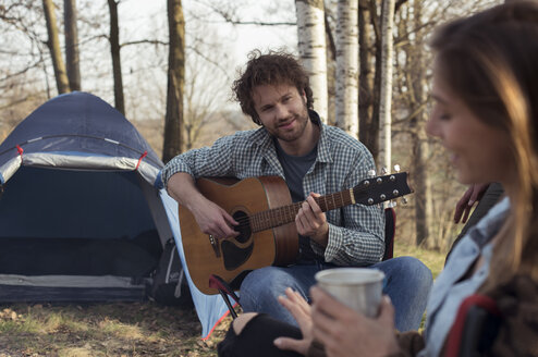 Couple camping in forest with man playing guitar - ZOCF00521
