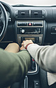 Woman putting her hand on man's hand using gear shift in car - DAPF00805