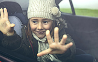 Portrait of happy little girl with wool cap putting her fingers on car window - DAPF00814