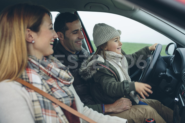 Happy family in car with little girl on father's lap pretending to drive - DAPF00817