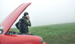 Man talking on cell phone next to broken car - DAPF00820