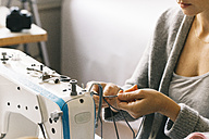 Close-up of woman using sewing machine - JUBF00278
